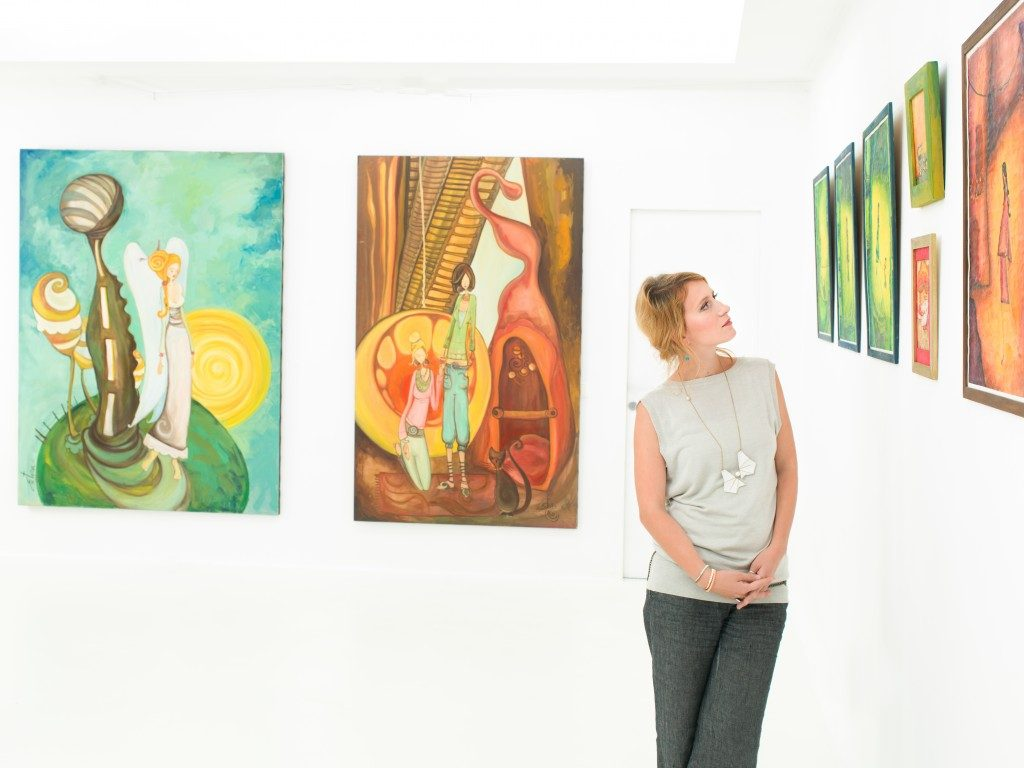 woman in art gallery leaning against a wall with colorful paintings