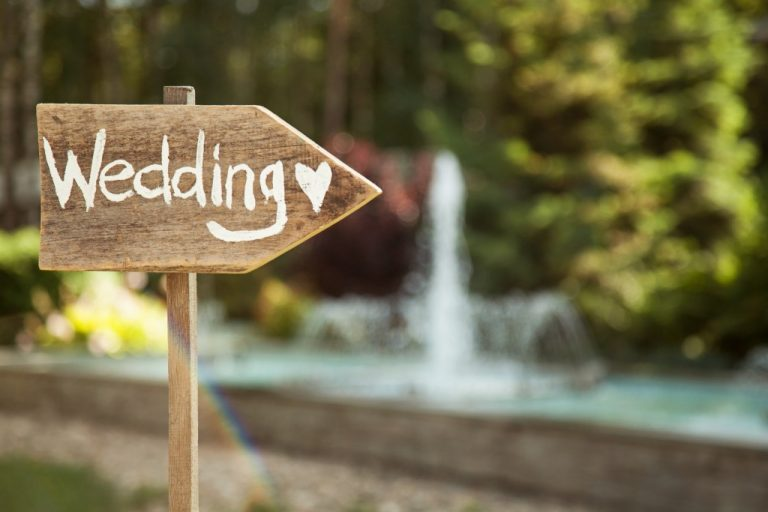 sign that points to wedding