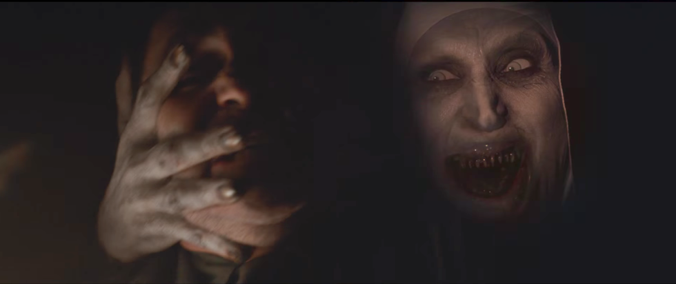 Valak holding a man's face