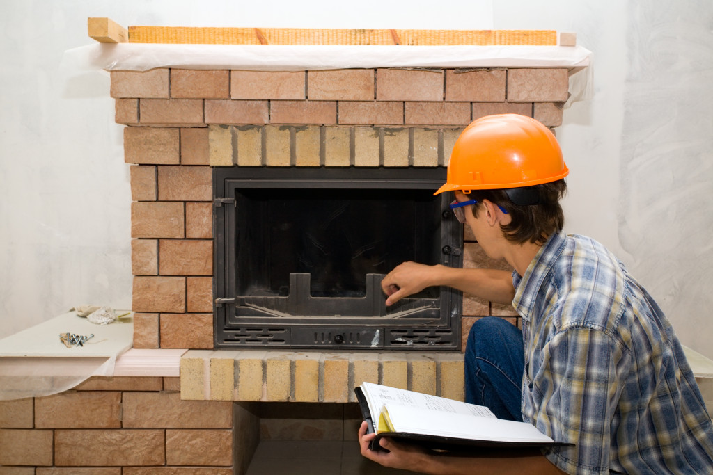 a person inspecting a fireplace
