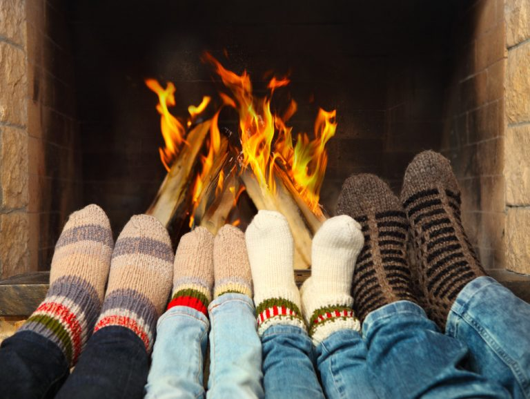 pairs of feet in front of a fireplace